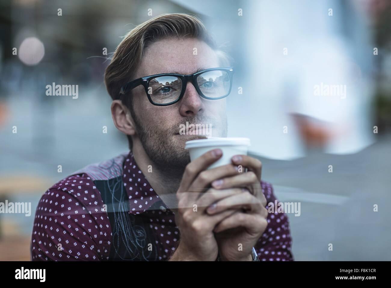 Triste giovane impreditore dietro la finestra della città a bere il caffè da asporto Immagini Stock