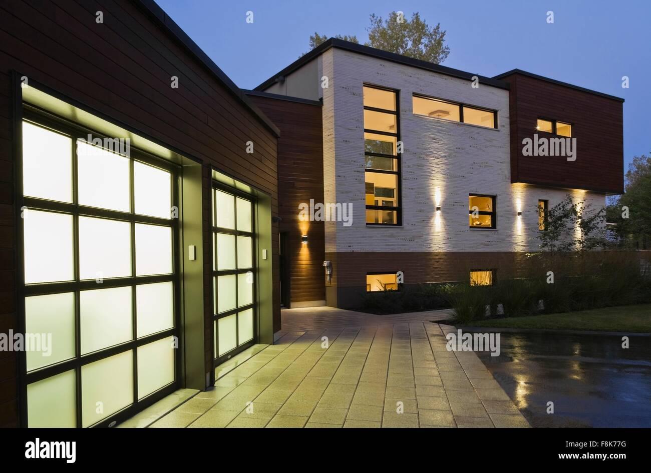 Illuminata due garage auto del moderno stile cubista casa residenziale al crepuscolo, Quebec, Canada Immagini Stock