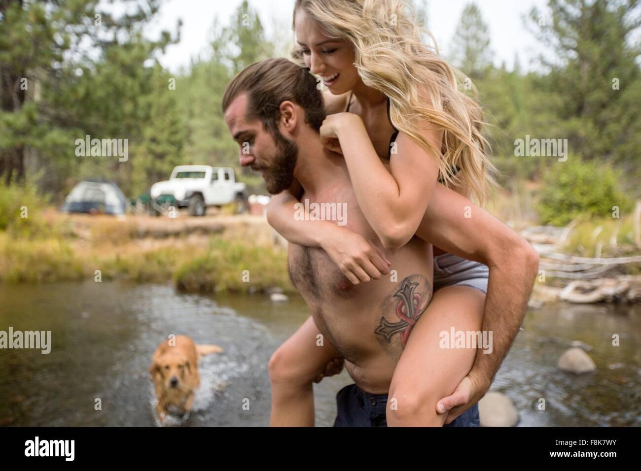 Giovane ragazza dando un piggyback Varcando il fiume, Lake Tahoe, Nevada, STATI UNITI D'AMERICA Foto Stock