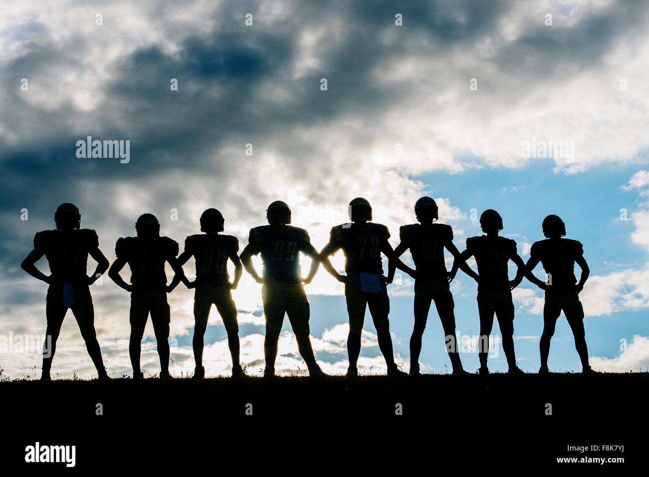 Silhouette di un gruppo di giovani american football giocatori, in piedi in fila, le mani sui fianchi Immagini Stock