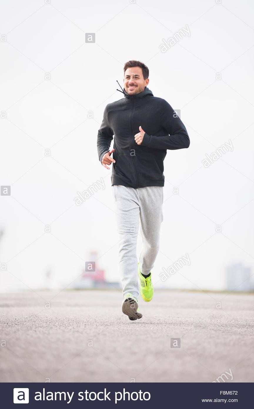 Felice giovane maschio runner in esecuzione in arena sportiva Immagini Stock