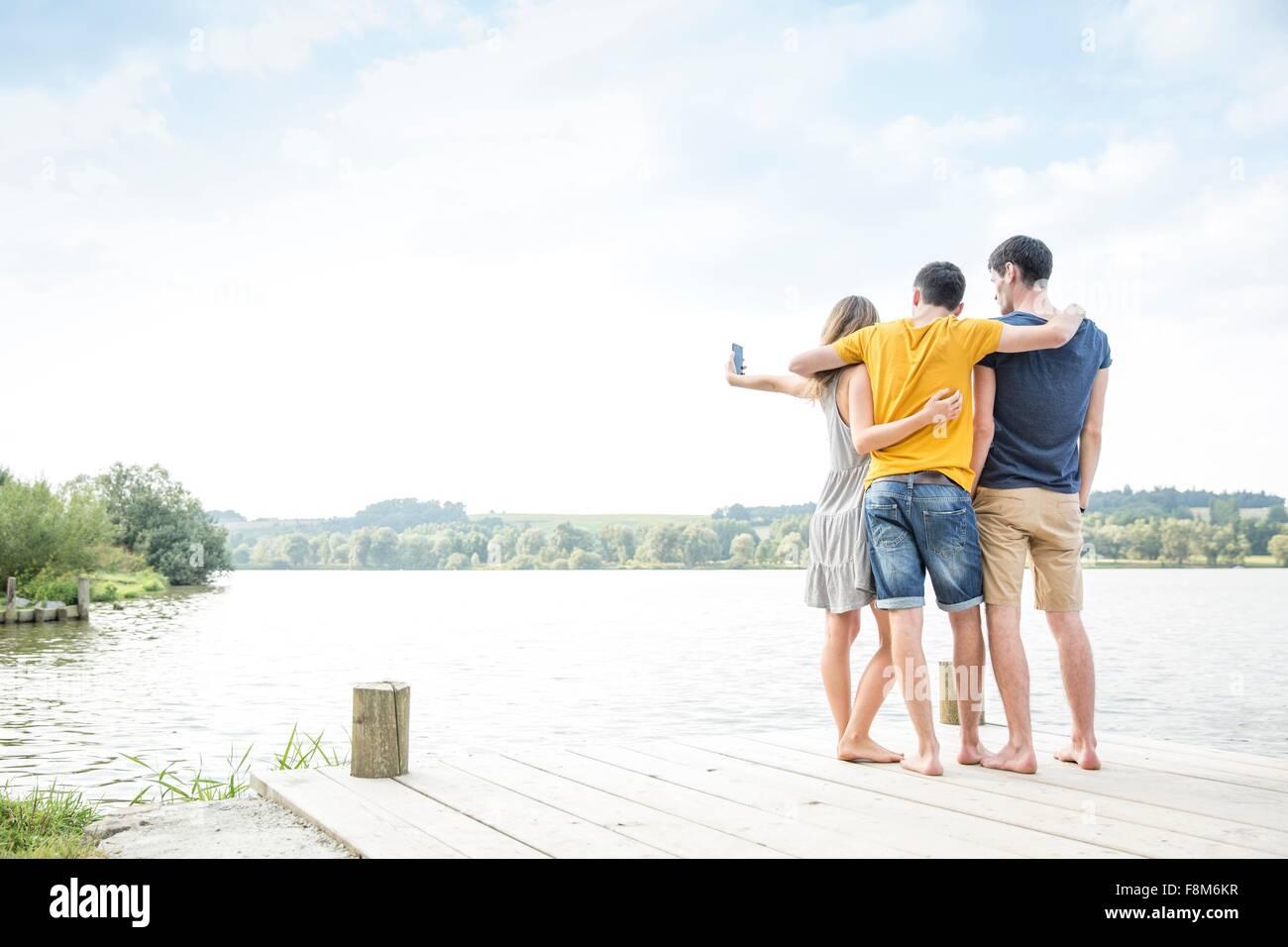 Tre giovani adulti in piedi sul molo, tenendo autoritratto, utilizza lo smartphone, vista posteriore Foto Stock