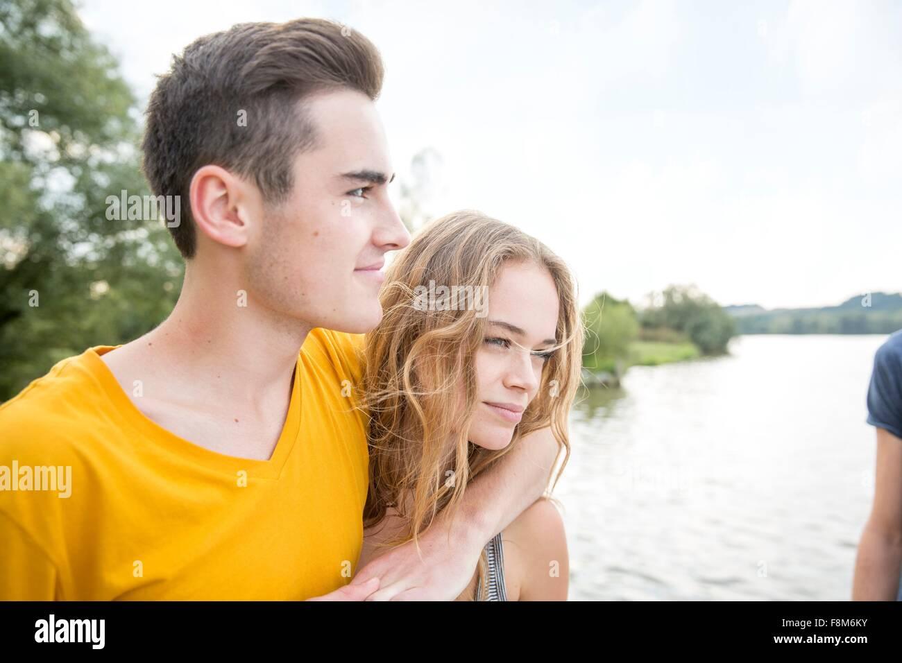 Coppia giovane accanto al lago, guardando a vista Immagini Stock
