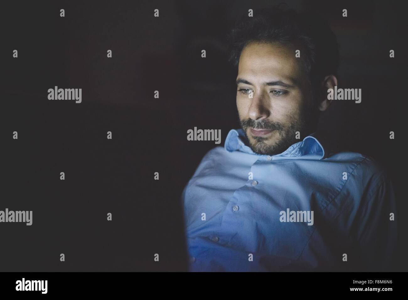Giovane uomo Pendente ritornare guardando giù illuminata da lo schermo del computer portatile Immagini Stock