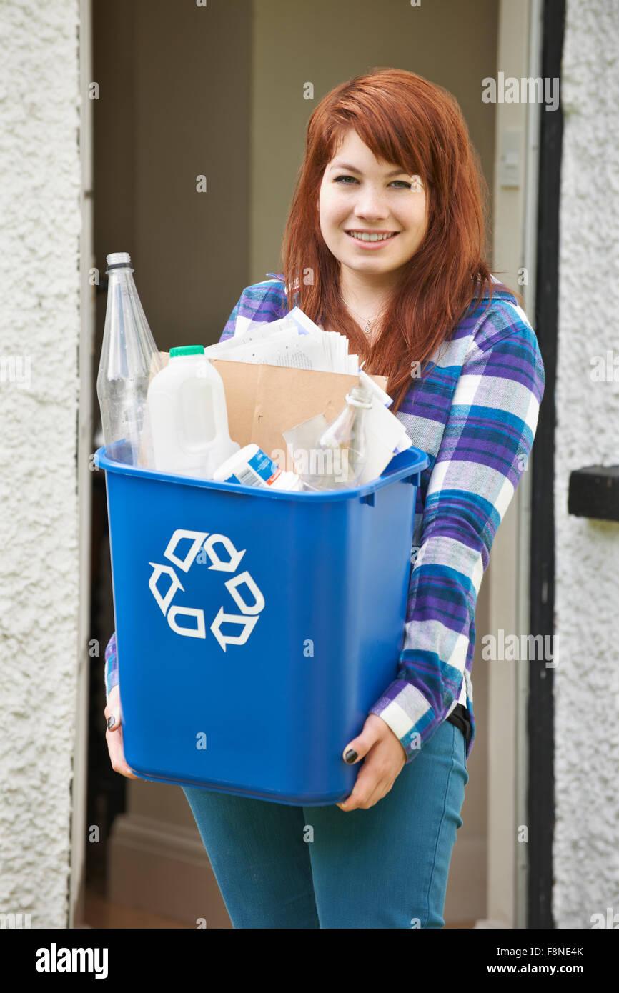 Ragazza adolescente lo svuotamento di riciclaggio a casa Immagini Stock