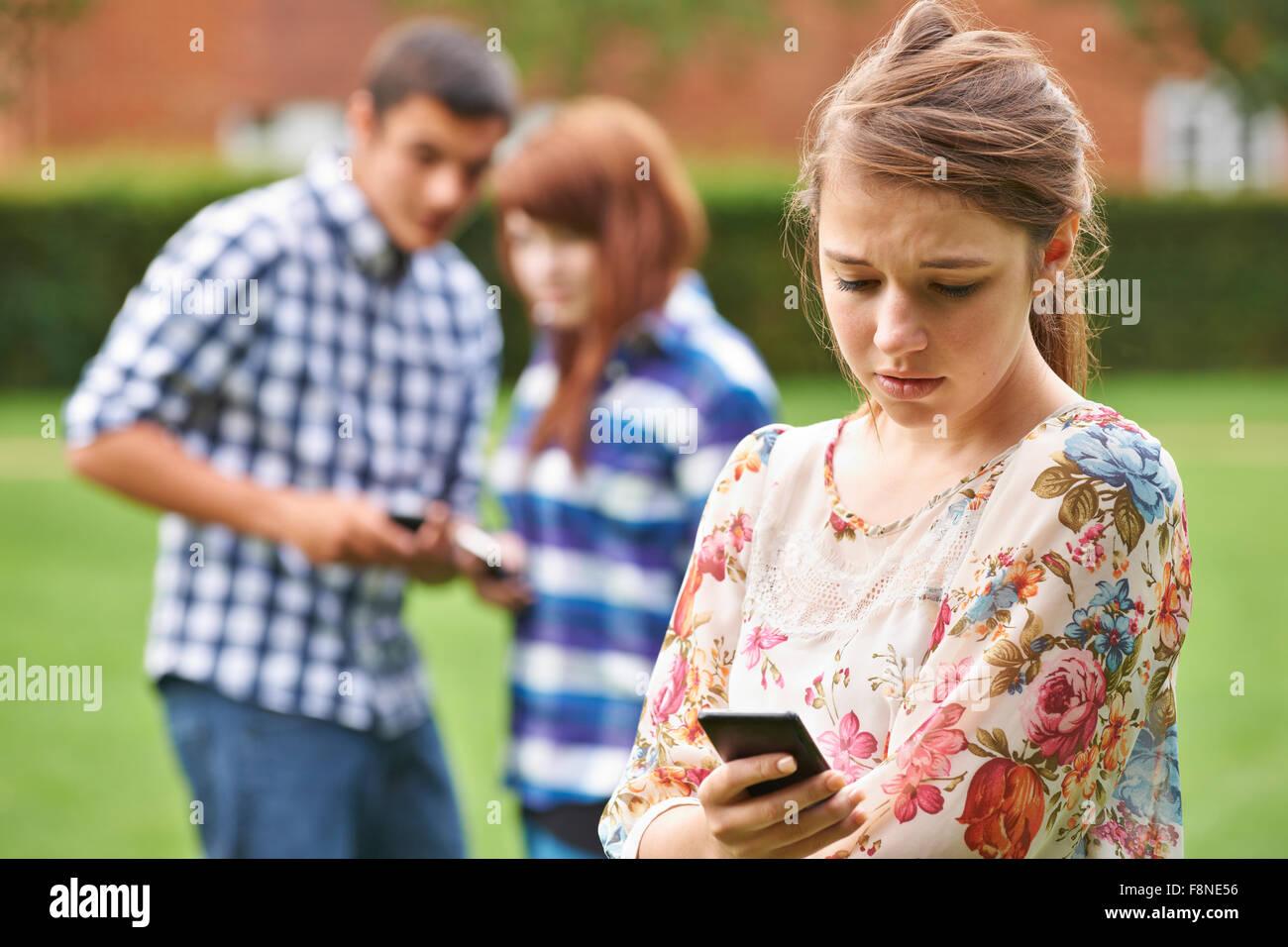 Ragazza adolescente vittima di bullismo mediante messaggio di testo Immagini Stock