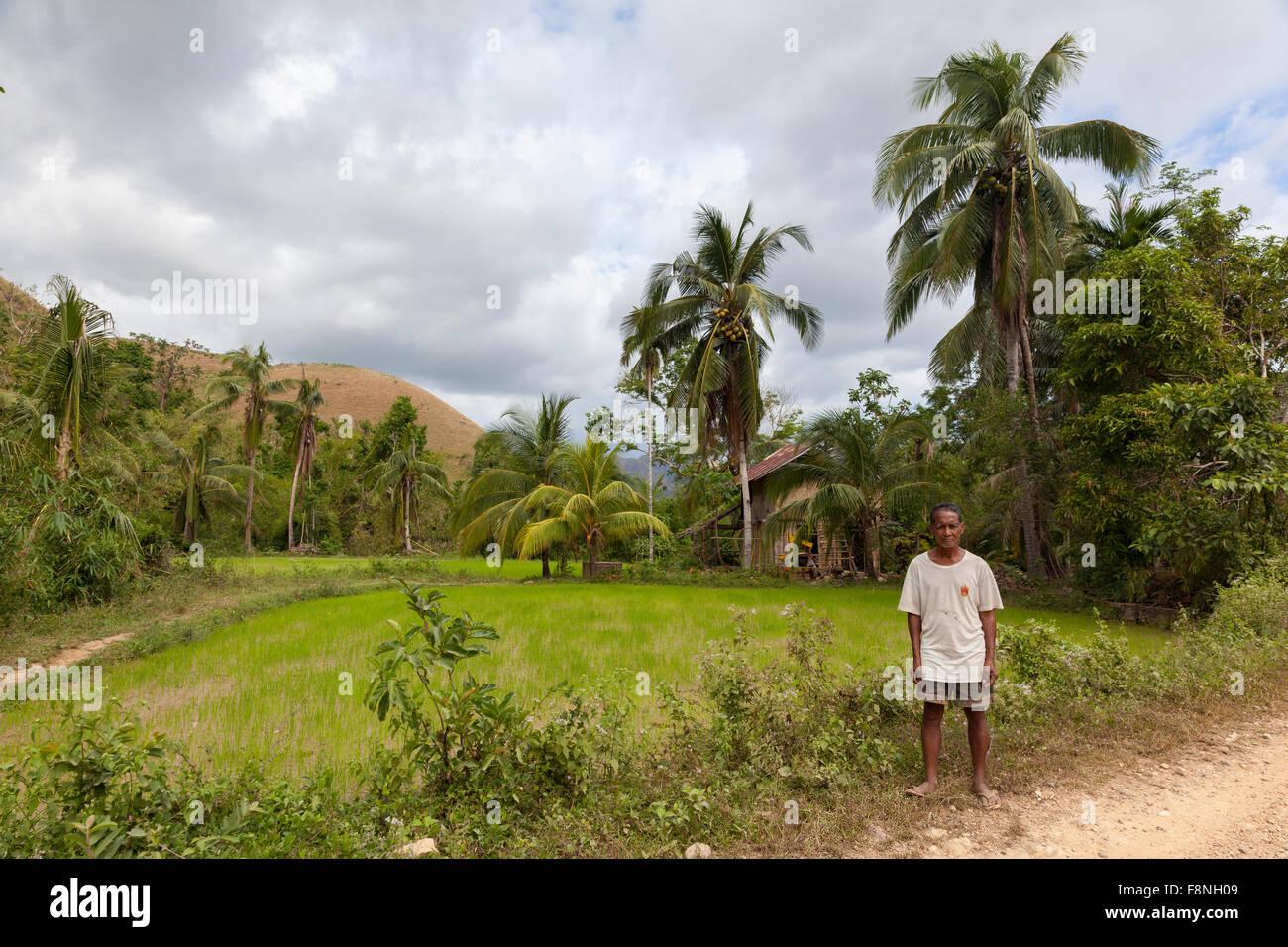 Un agricoltore in piedi dal suo le risaie e la sua casa Immagini Stock