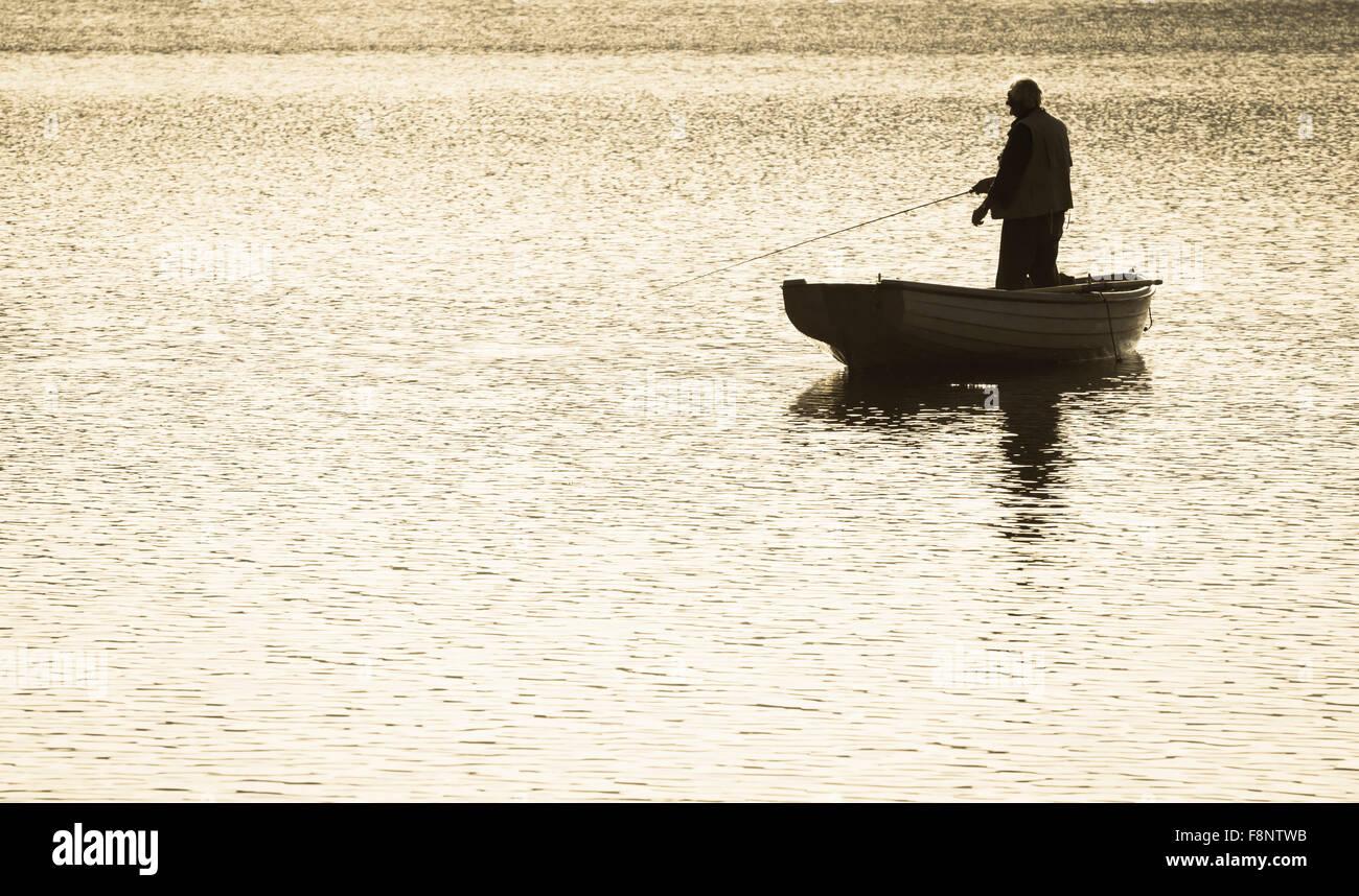 Uomo di Pesca a Mosca Report di Pesca dalla Barca sul serbatoio Immagini Stock