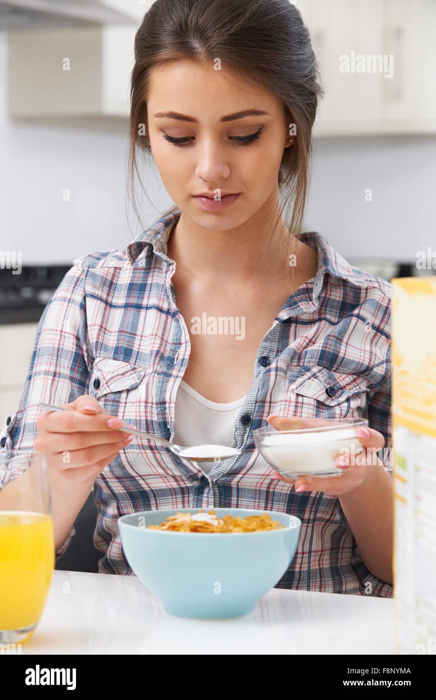 Ragazza adolescente aggiungendo lo zucchero di cereali per la prima colazione Immagini Stock