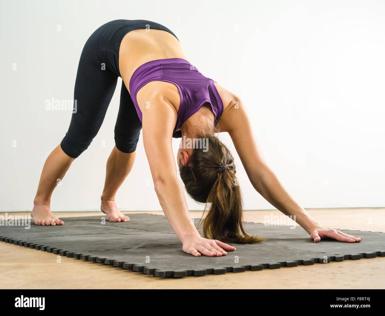 Foto di un sano giovane donna facendo il cane verso il basso posizione di yoga su un tappetino nero. Immagini Stock