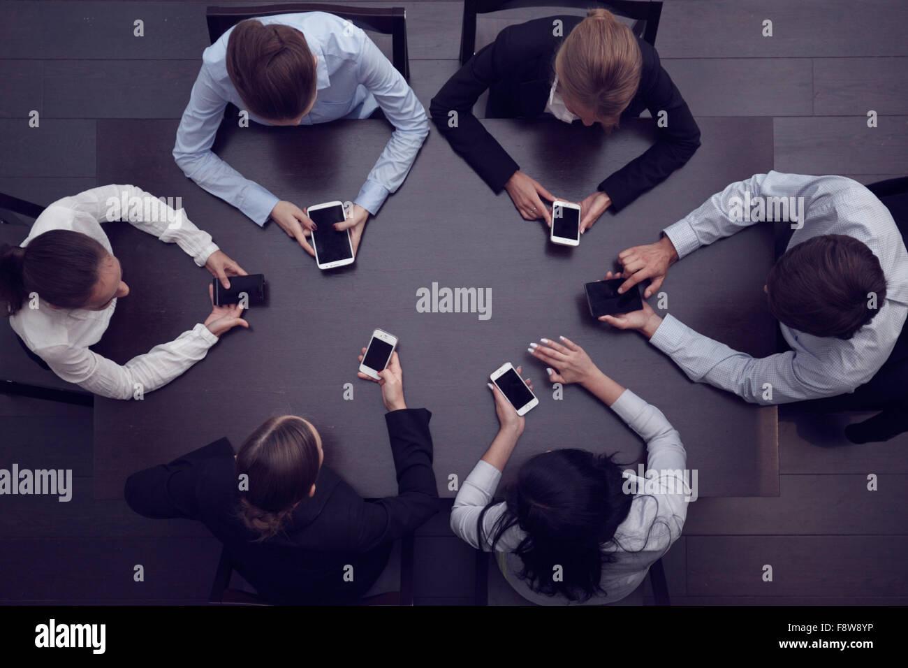 La gente di affari con gli smartphone seduti attorno al tavolo, vista dall'alto Immagini Stock