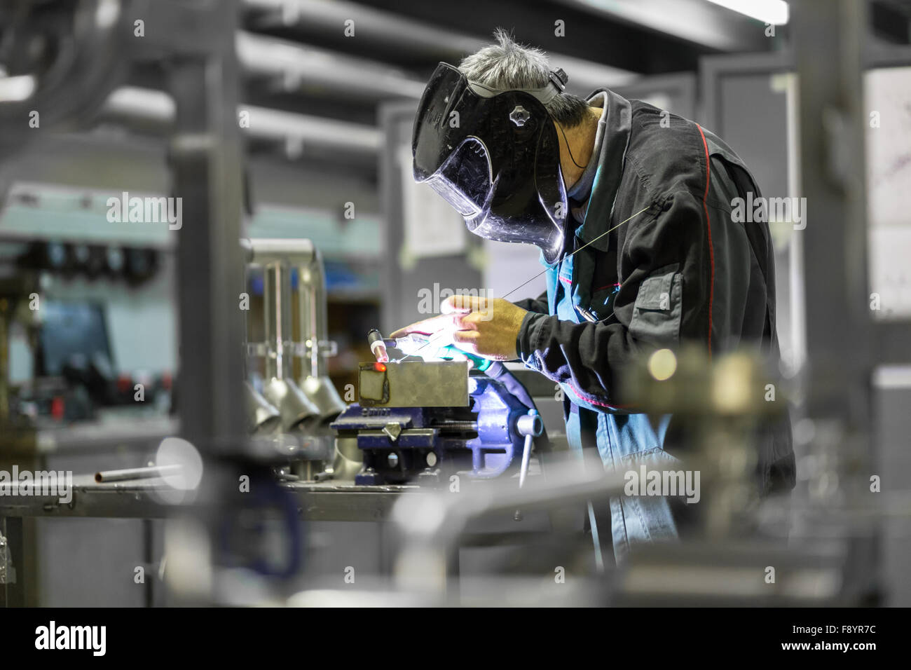 Operaio industriale saldatura in fabbrica di metallo. Immagini Stock