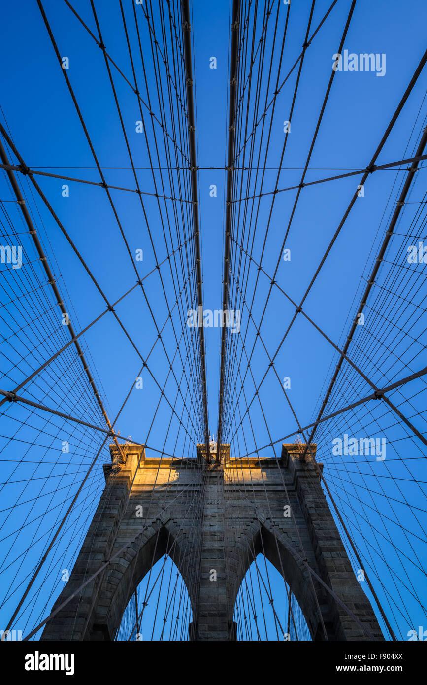 Brooklyn Bridge tower con doppio archi gotici e simmetrica dei cavi di sospensione al tramonto con il cielo azzurro, Foto Stock