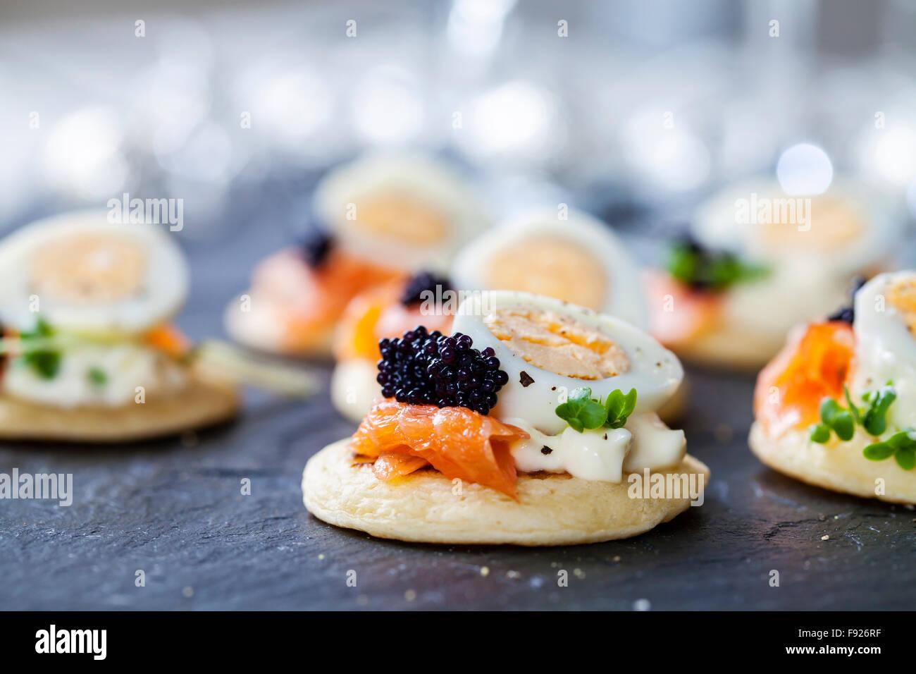 Parte cibo, blinis con salmone, uova di quaglia e caviale Foto Stock