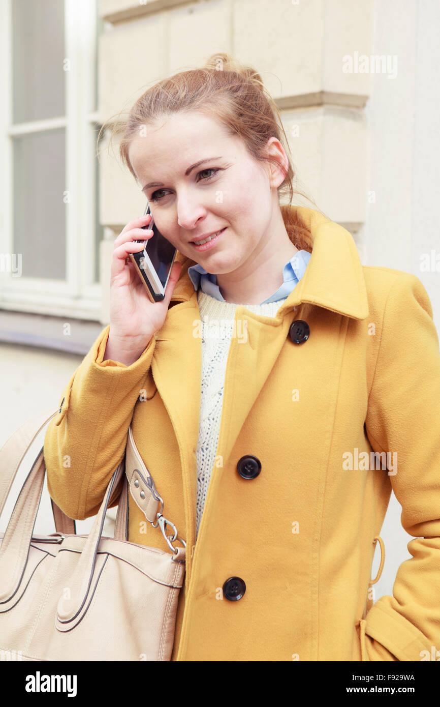 Donna in cappotto giallo parlando al telefono cellulare Immagini Stock