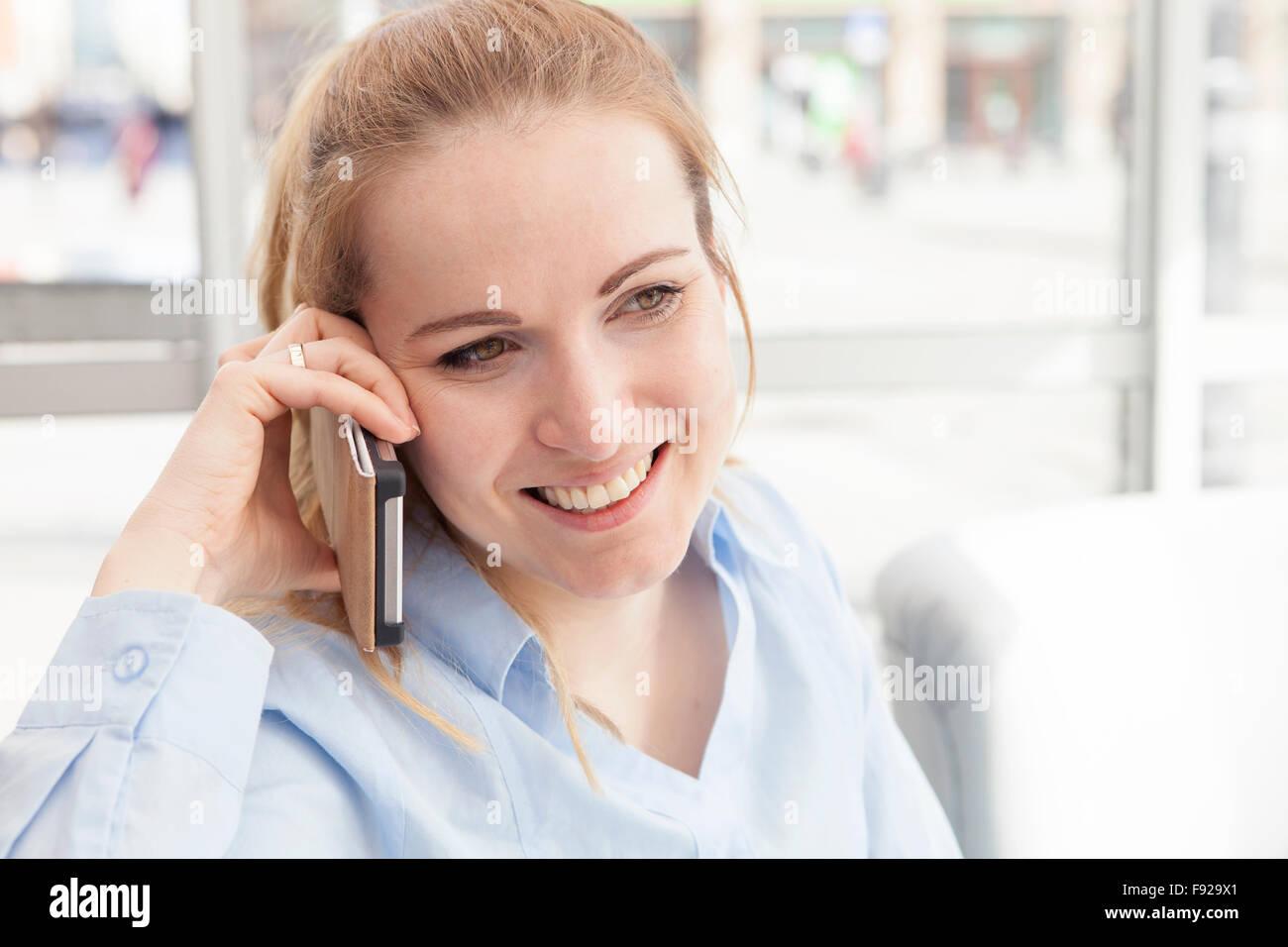 Donna che parla al telefono nel cafe Immagini Stock