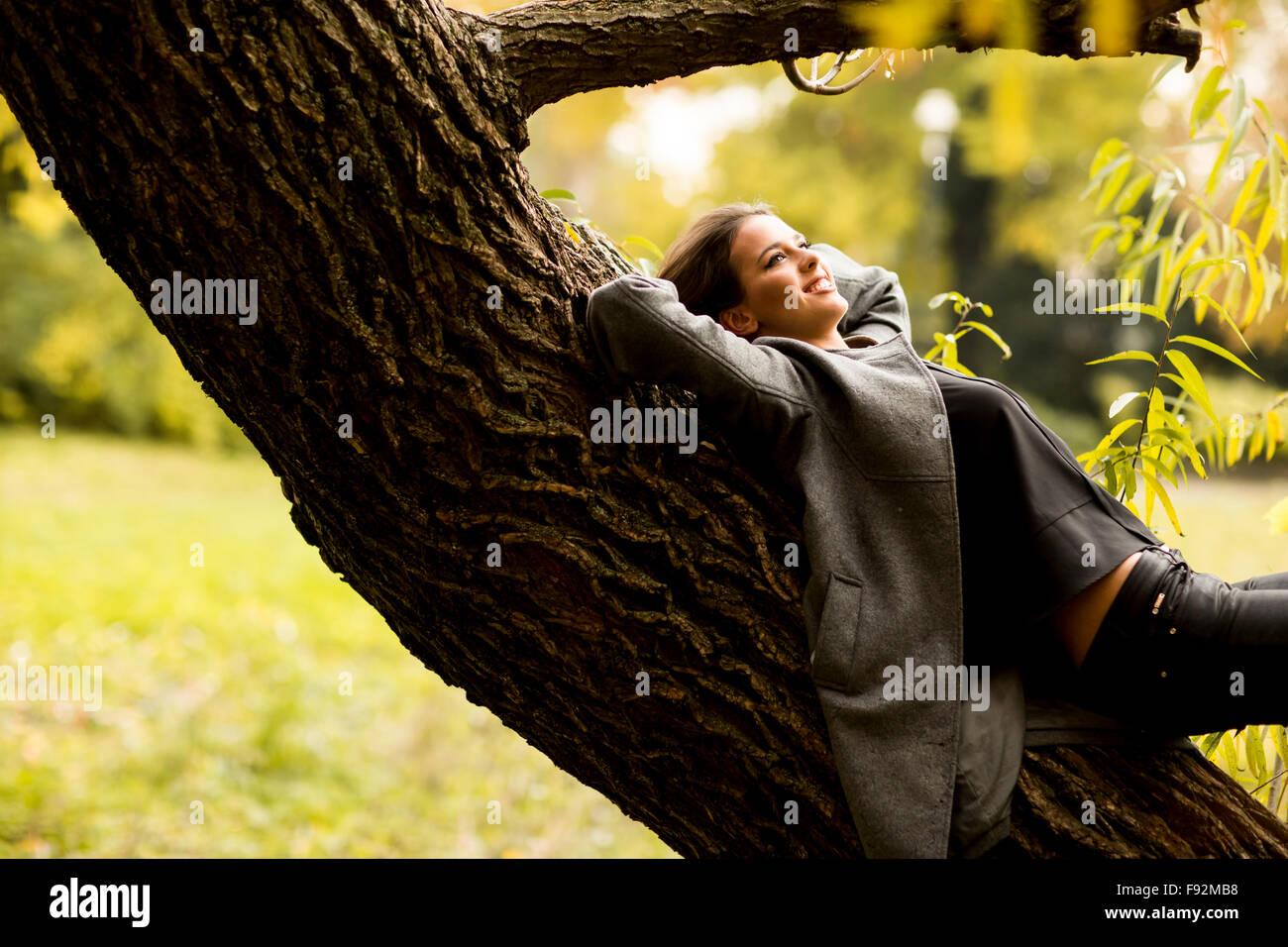 Oung donna in appoggio sulla struttura ad albero Immagini Stock