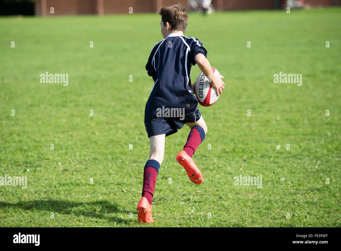 Istruzione secondaria Wales UK: educazione fisica lezione - un ragazzo adolescente giocando a rugby su una scuola Immagini Stock