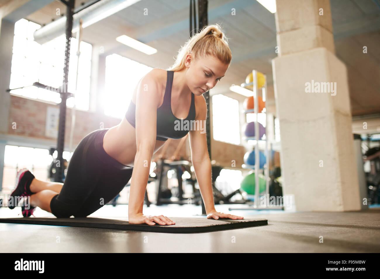 Attraente giovane femmina facendo spingere ups su esercizio mat. Donna Fitness allenarsi in palestra. Immagini Stock