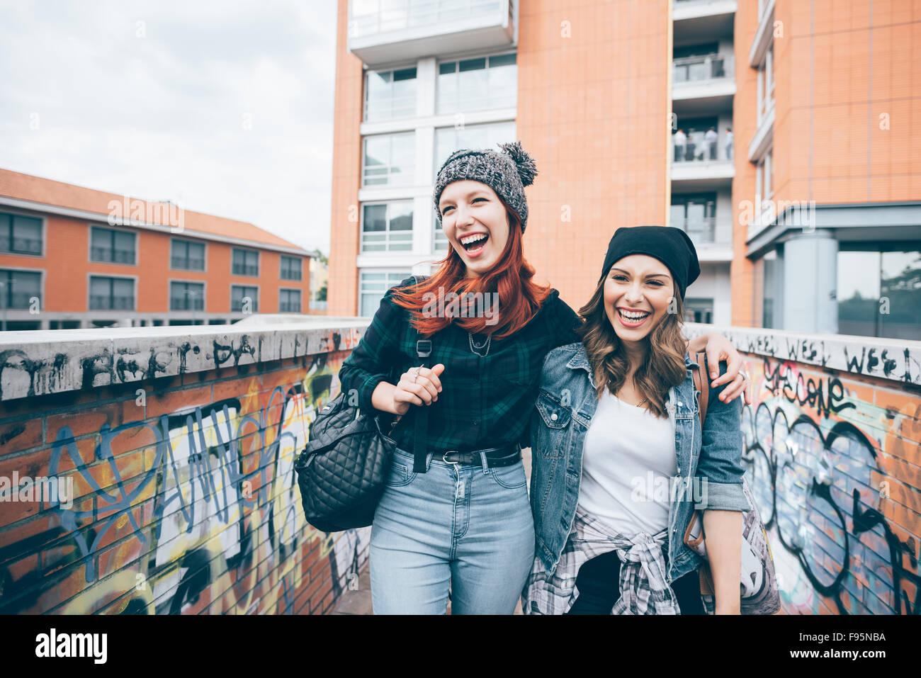 Ginocchio la figura dei due giovani caucasici bello biondo e redhead capelli dritti donne abbracciando a piedi all'aperto Immagini Stock