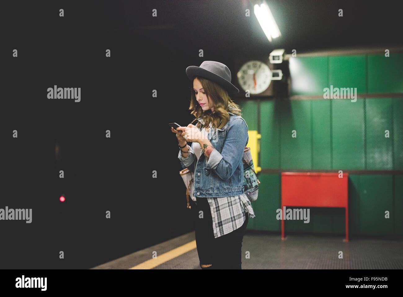 Giovane bella bionda caucasica capelli dritti donna in attesa in metropolitana per tubo utilizza lo smartphone guardando Immagini Stock