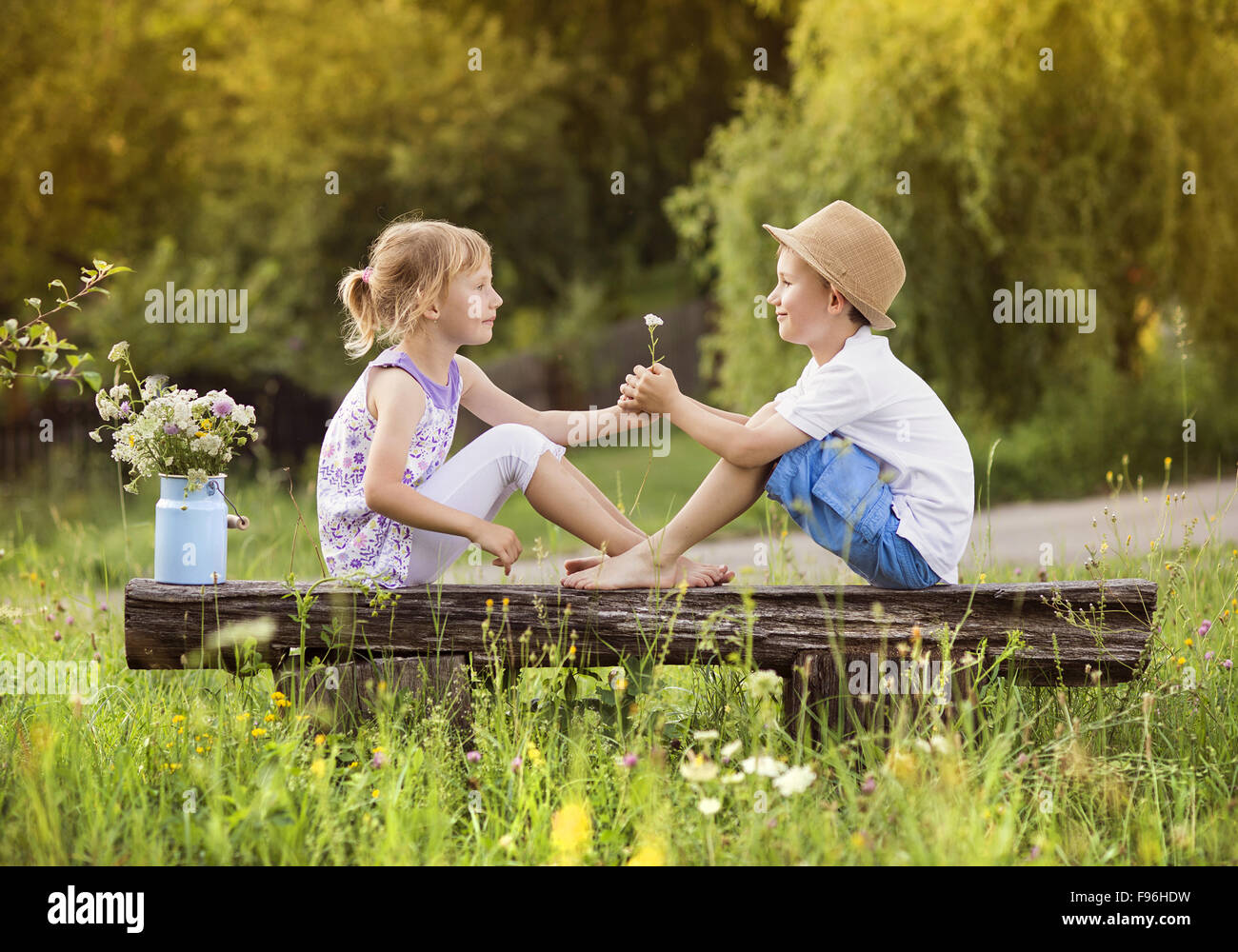 Carino un ragazzo e una ragazza in amore. Essi seduta sul banco al tramonto. Immagini Stock