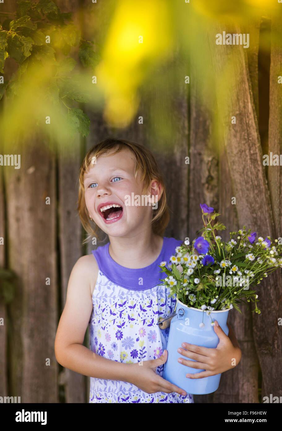 Bimba bionda azienda fiori di prato ridere da recinzione di legno Immagini Stock