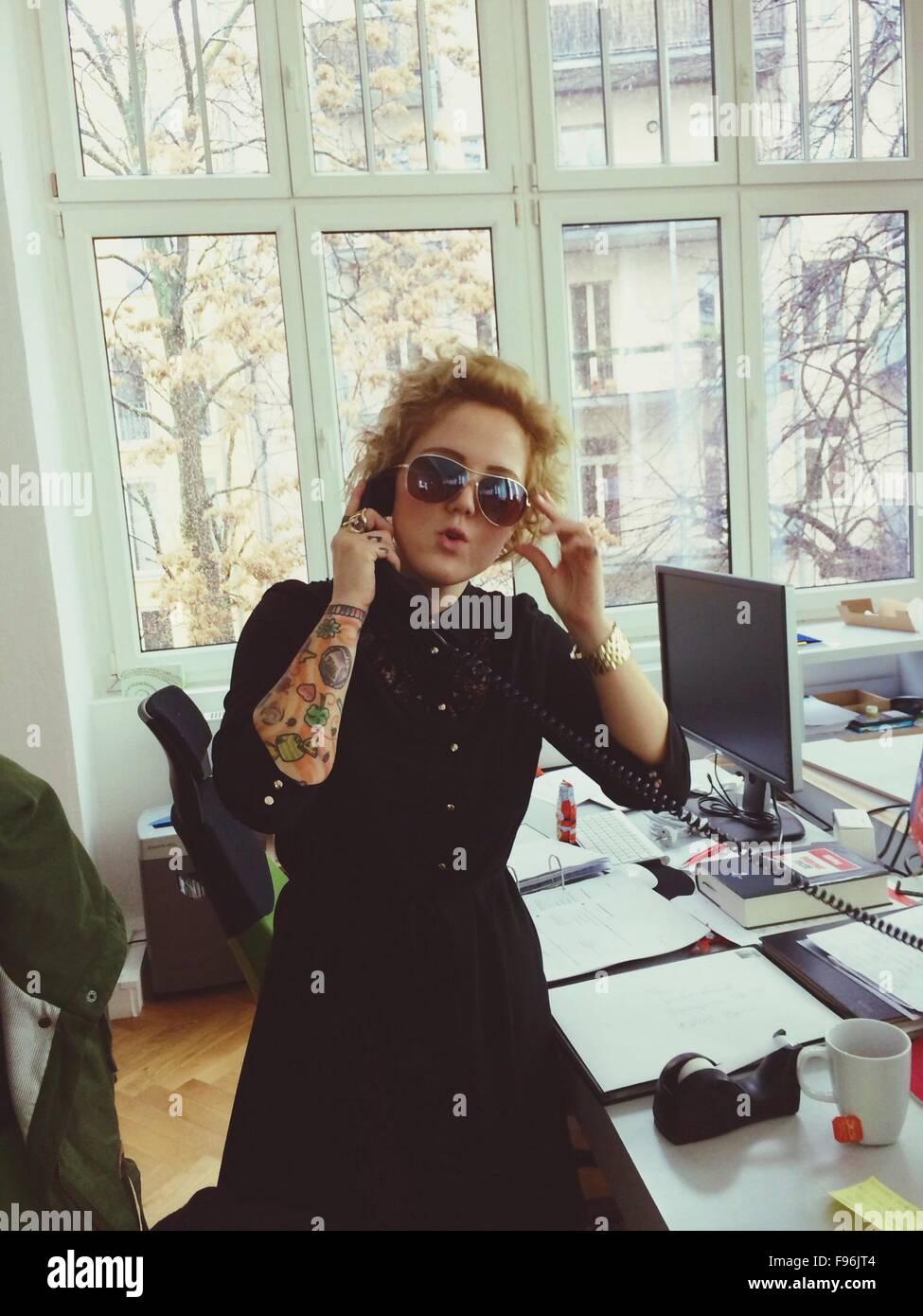 Ritratto di moda giovane donna parlando in telefono in ufficio Immagini Stock
