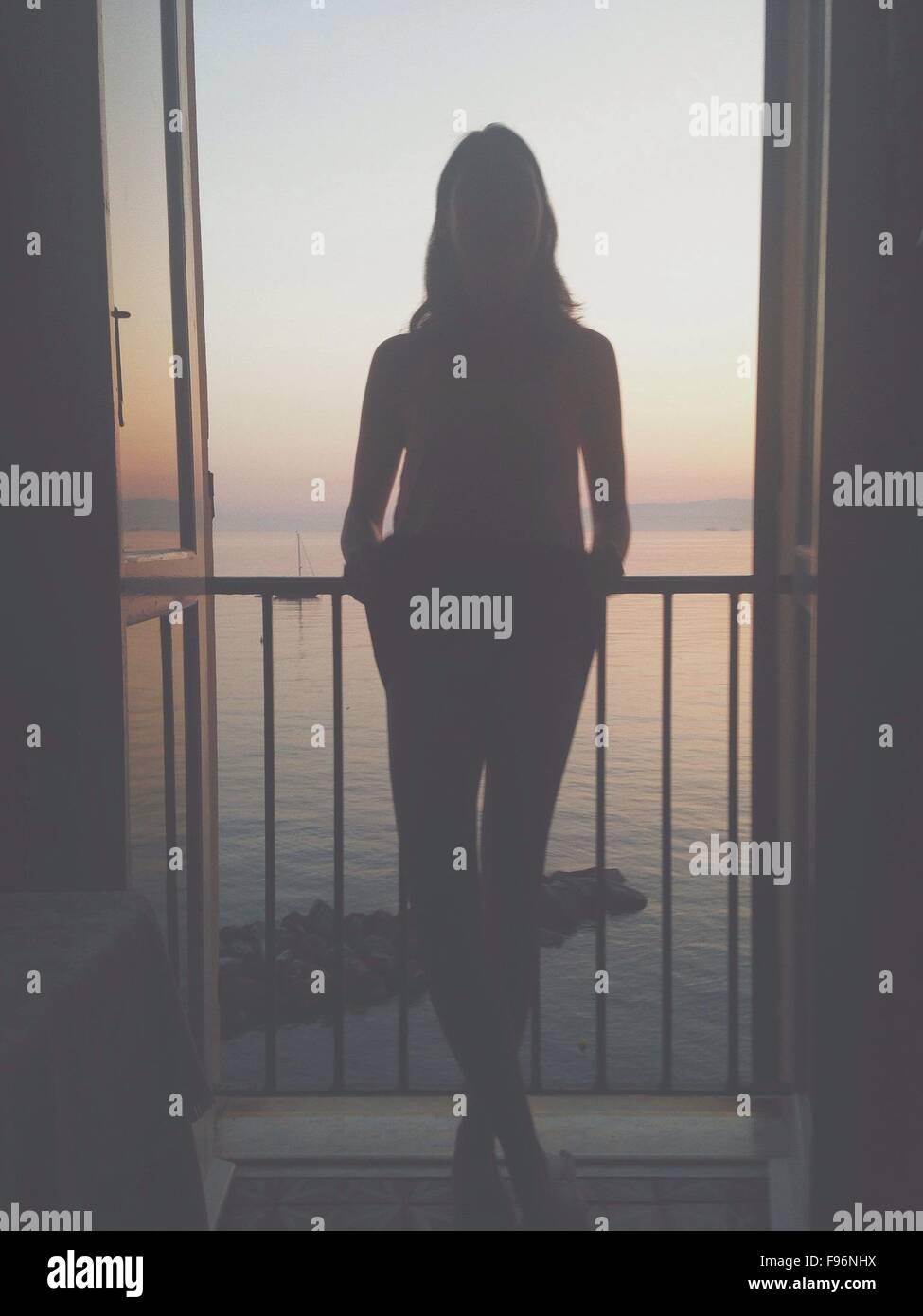 Silhouette donna in piedi sul balcone contro il mare Immagini Stock