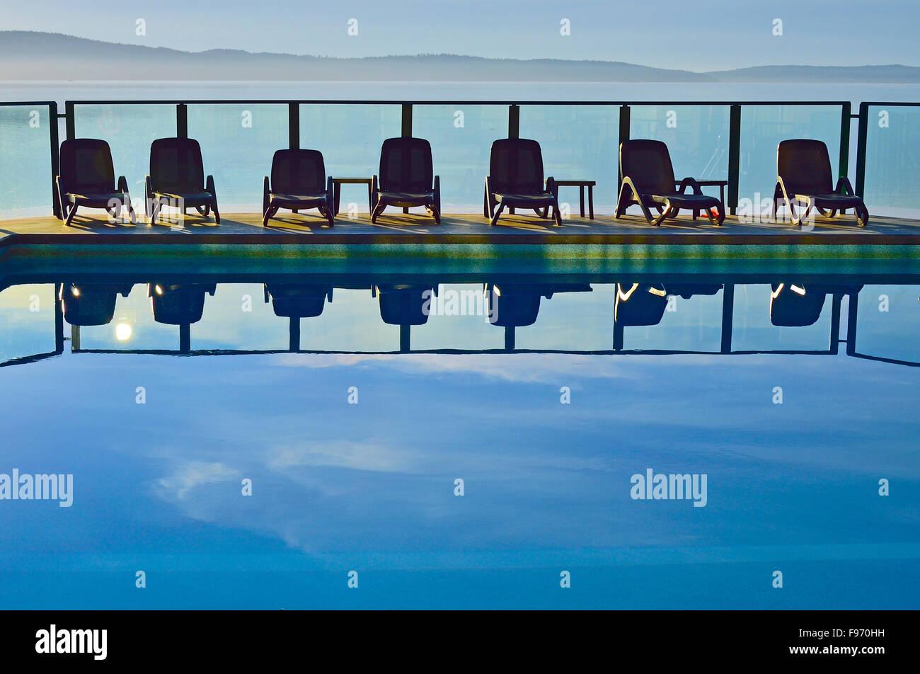 Un'immagine orizzontale di una linea di sedie in una piscina esterna al vacation resort sull'Isola di Vancouver Immagini Stock