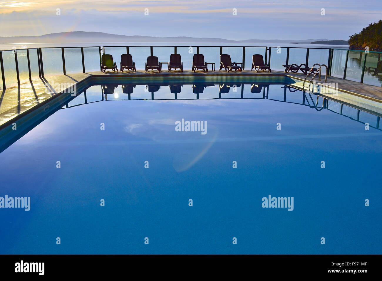 Un'immagine orizzontale di una piscina esterna con una linea di sedie in un villaggio vacanza sull'Isola Immagini Stock