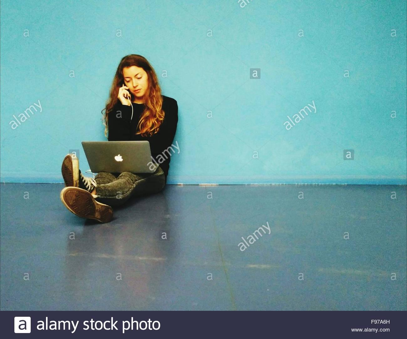 Giovane donna parlando al telefono mentre è seduto sul pavimento con il computer portatile Immagini Stock