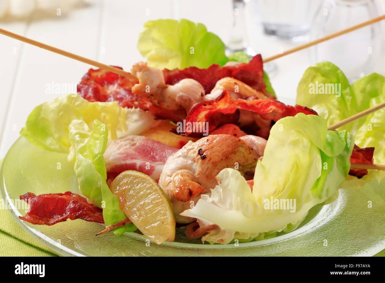 Pollo satay con strisce di pancetta e lattuga Immagini Stock
