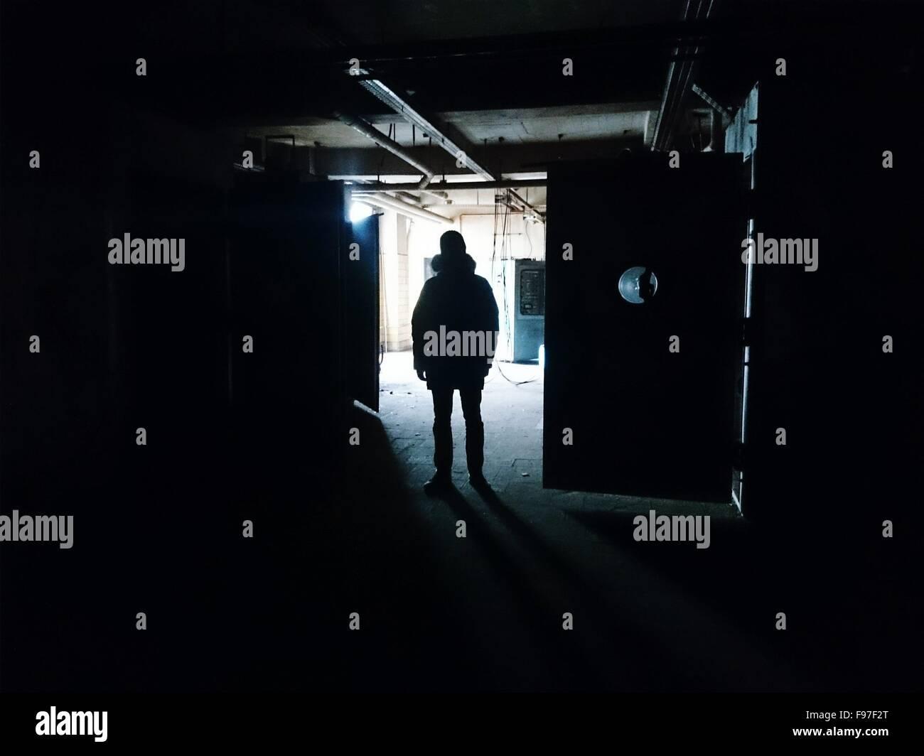 Silhouette di un uomo in piedi in edificio scuro Immagini Stock