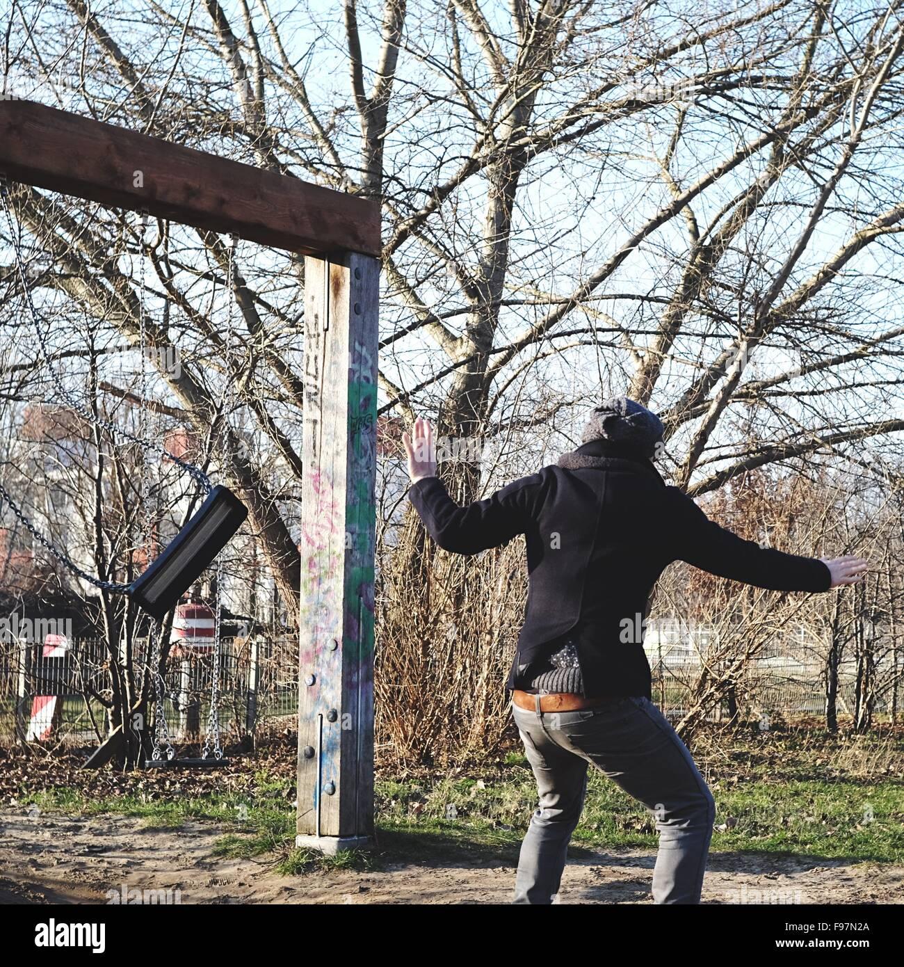 Vista posteriore dell'uomo a giocare con lo swing Immagini Stock