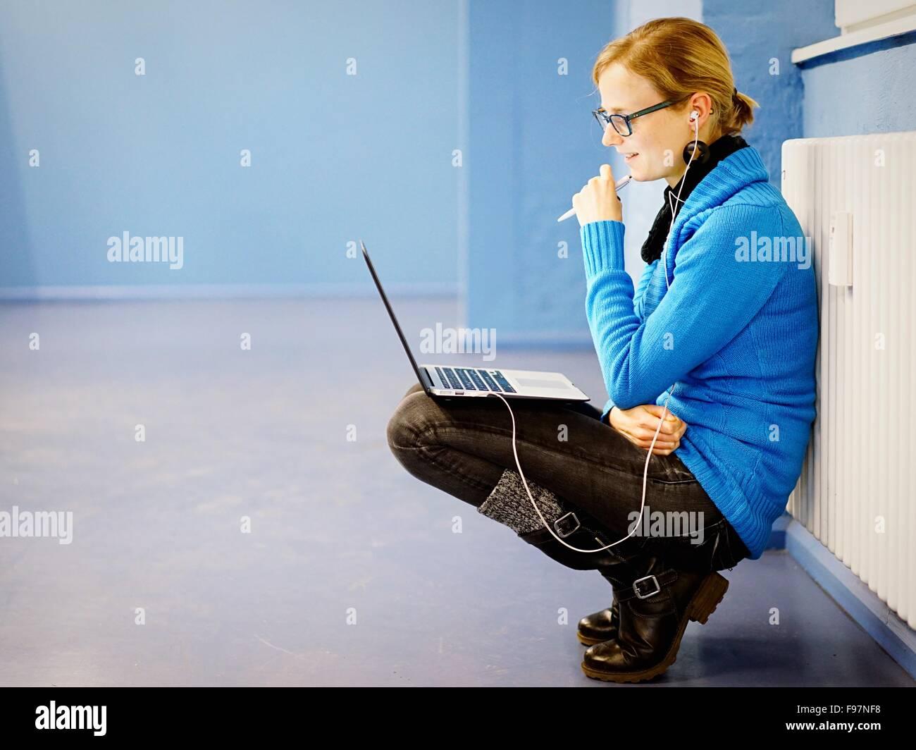 Vista laterale della donna seduta sul pavimento con il computer portatile Immagini Stock
