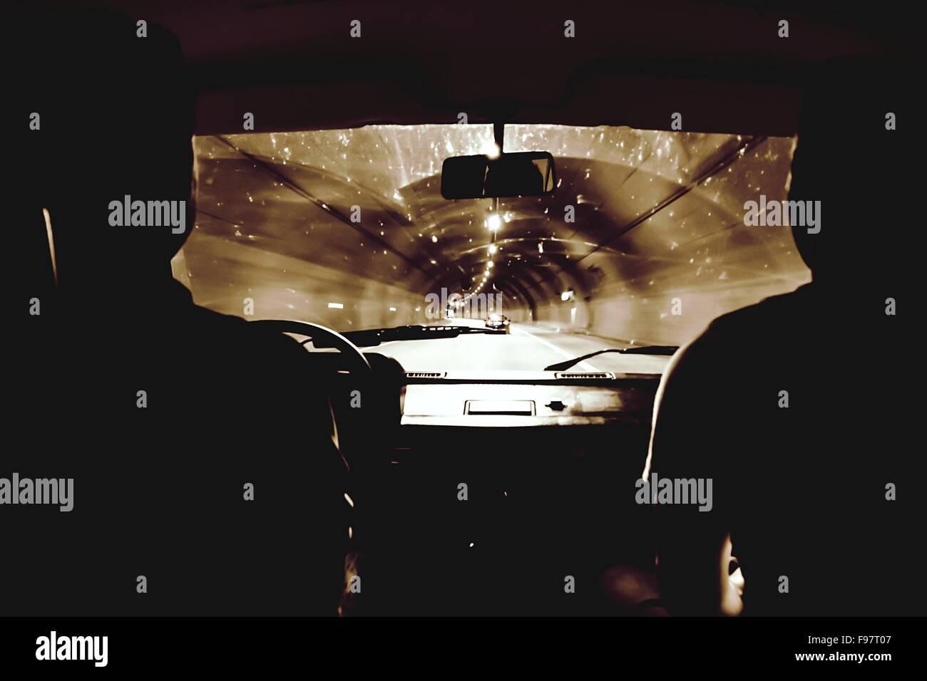 Silhouette persone guida auto nel tunnel illuminato Immagini Stock