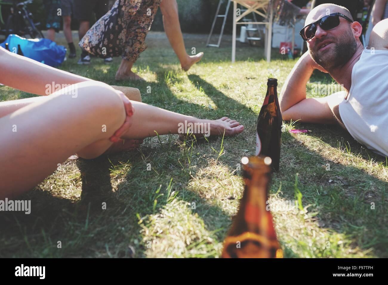 Uomo e donna con bottiglie di birra in posizione di parcheggio Immagini Stock