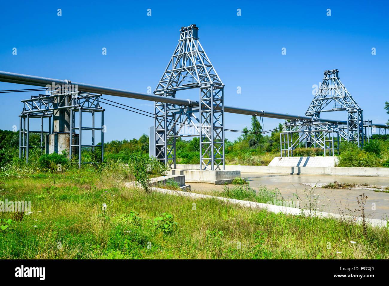 Tubazione gas di linee che prevista attraverso il fiume fangoso e foresta verde in scenario estivo, Romania. Immagini Stock