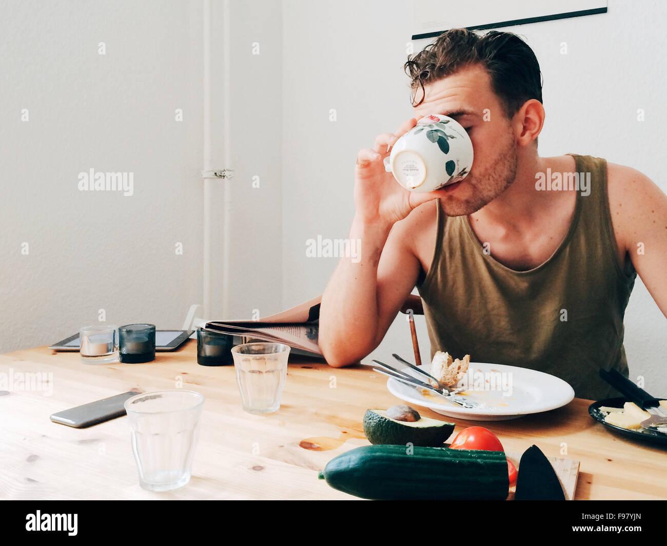Uomo di bere il caffè da tavolo disordinato Immagini Stock