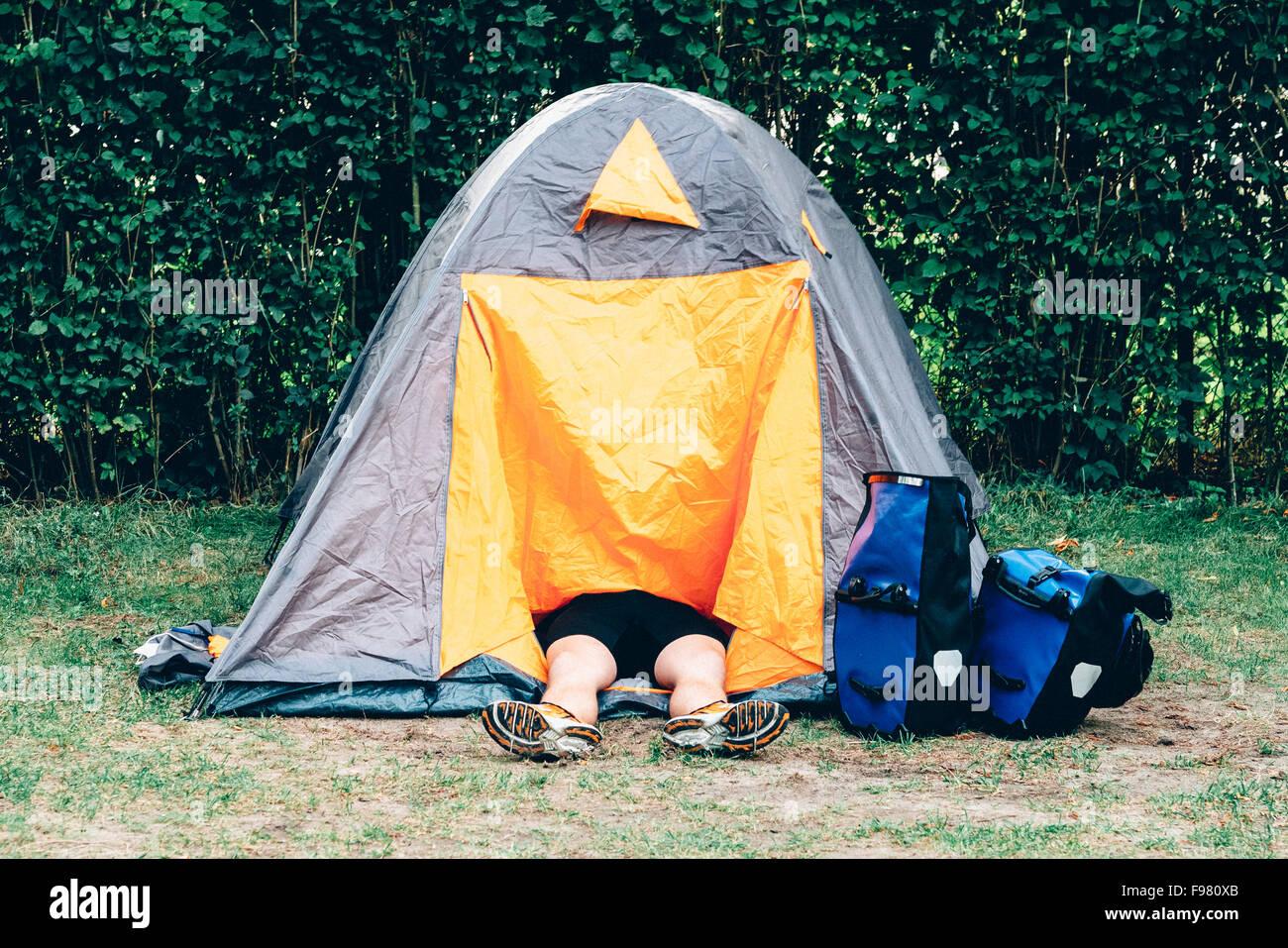 Sezione bassa di persona a riposo in tenda in campo al Campeggio Immagini Stock