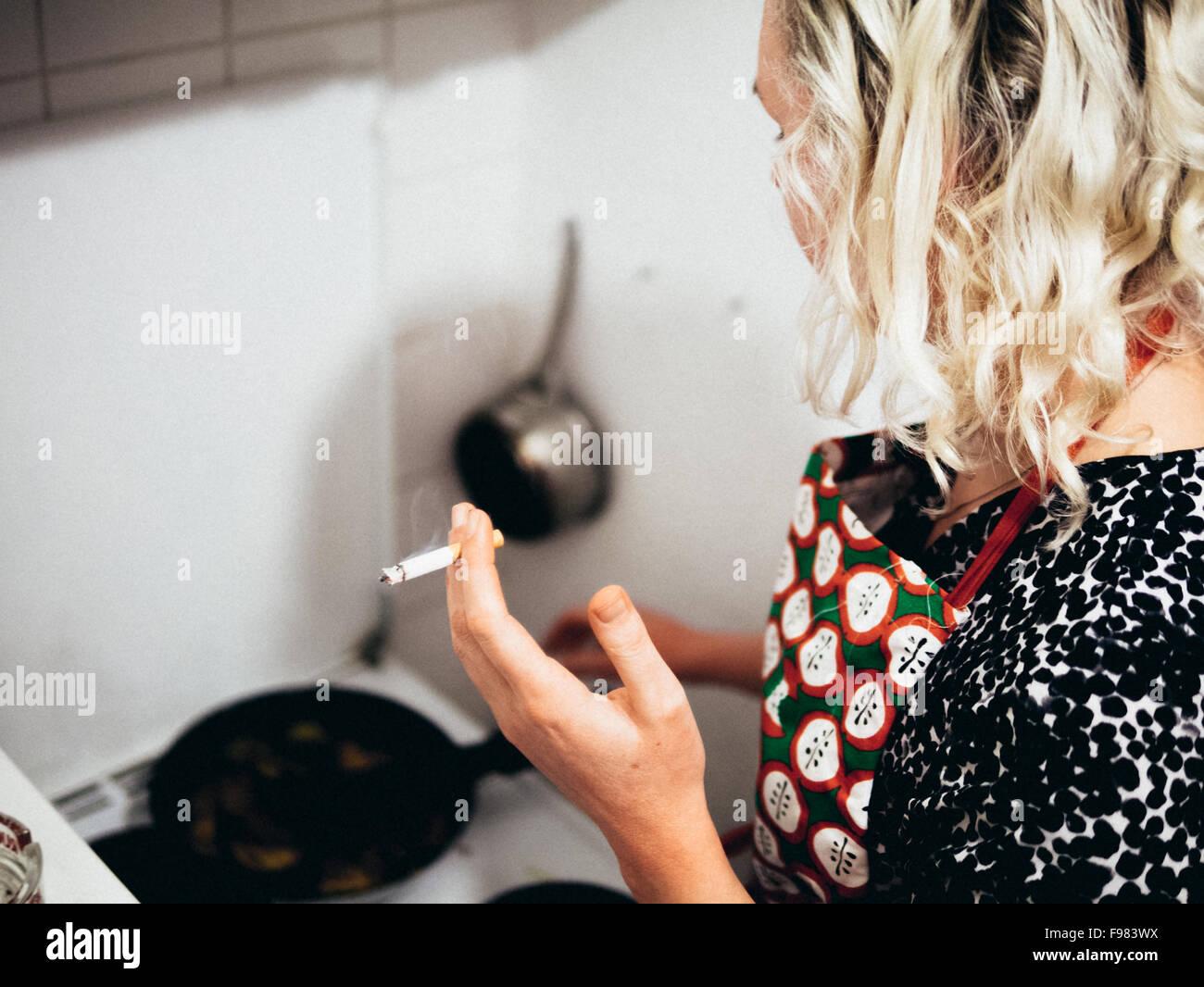 Elevato angolo di visione della donna Sigaretta fumare durante la cottura in cucina Immagini Stock
