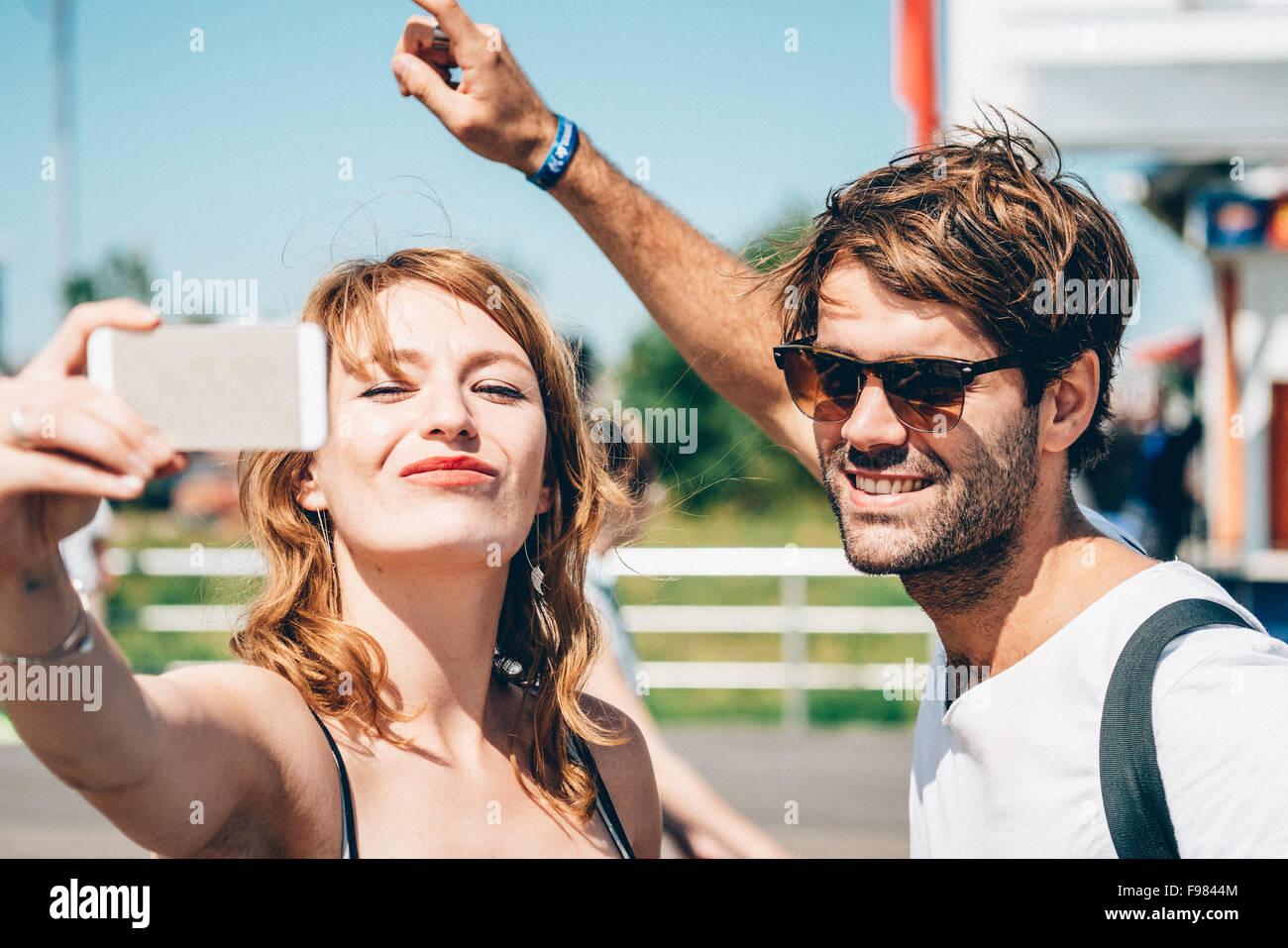 Happy amici facendo clic Selfie su Smart Phone permanente, mentre all'aperto Immagini Stock
