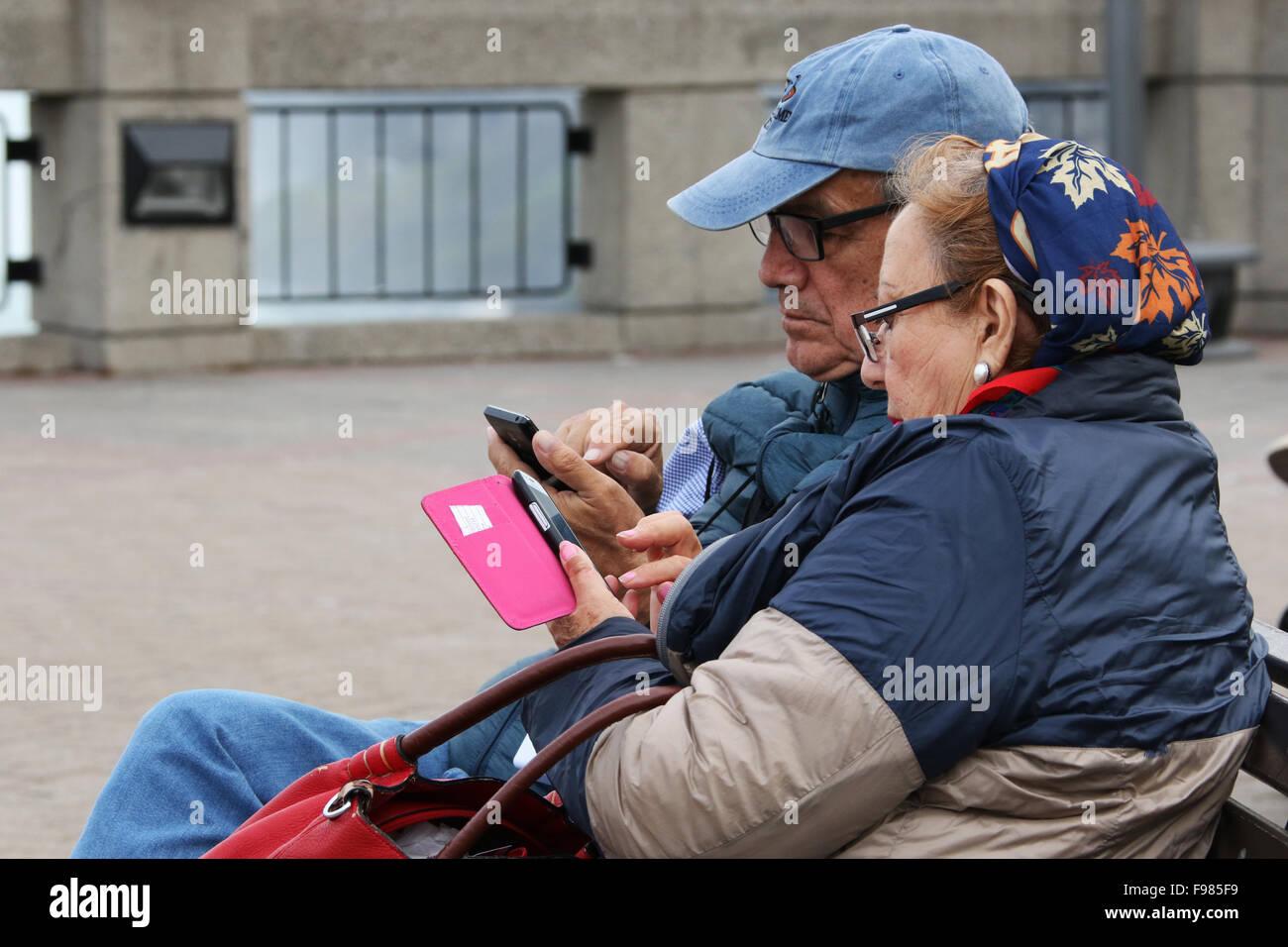 Gli anziani matura a Cascate Canadesi e di controllare i loro telefoni cellulari. Cascate Horseshoe. Vista da Niagara Immagini Stock