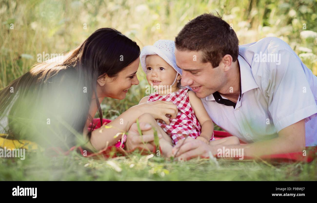 Felice giovane famiglia di trascorrere del tempo all'aperto su un giorno di estate Immagini Stock