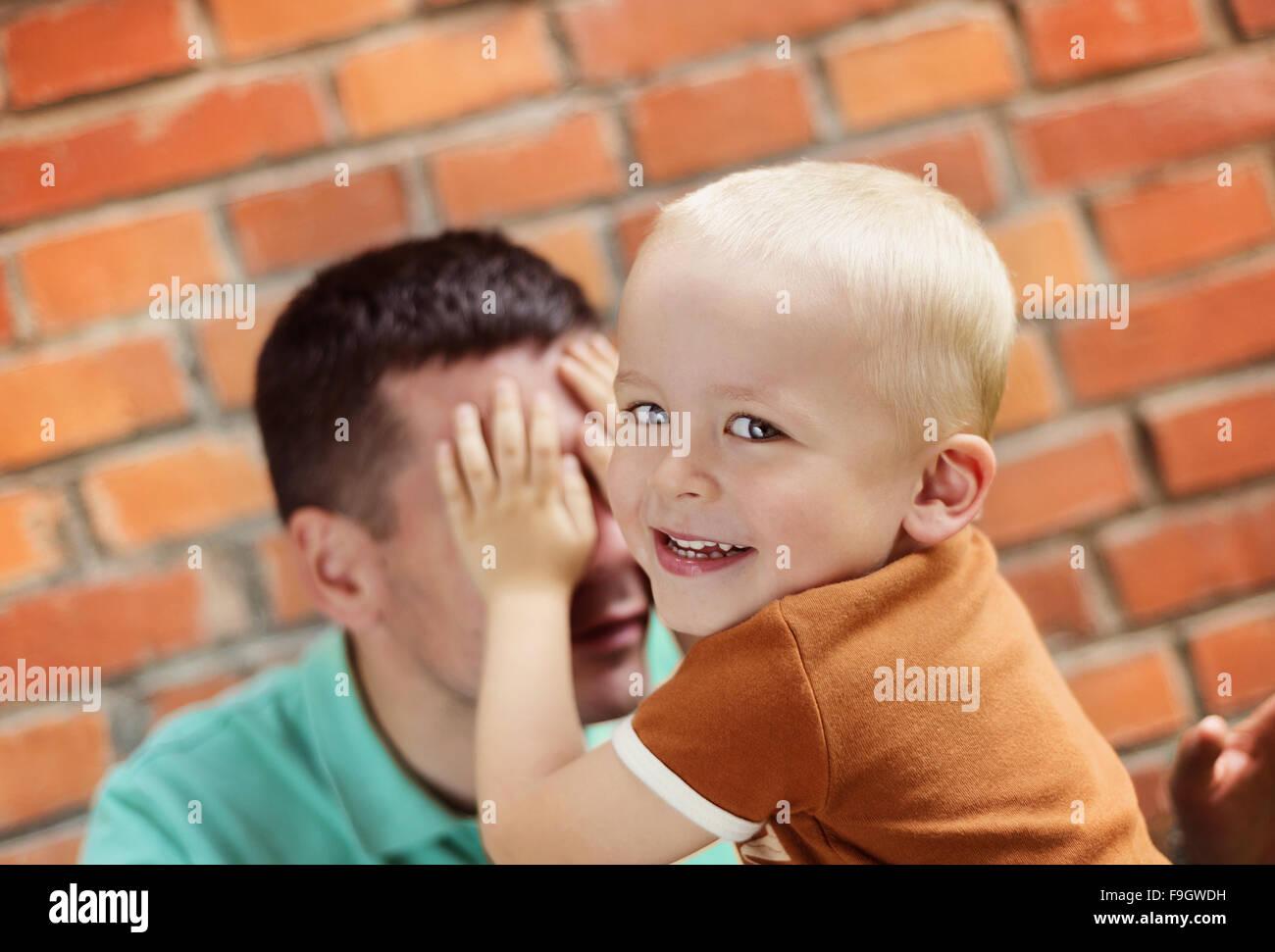 Padre e figlio facendo facce buffe insieme su un muro di mattoni in background Immagini Stock