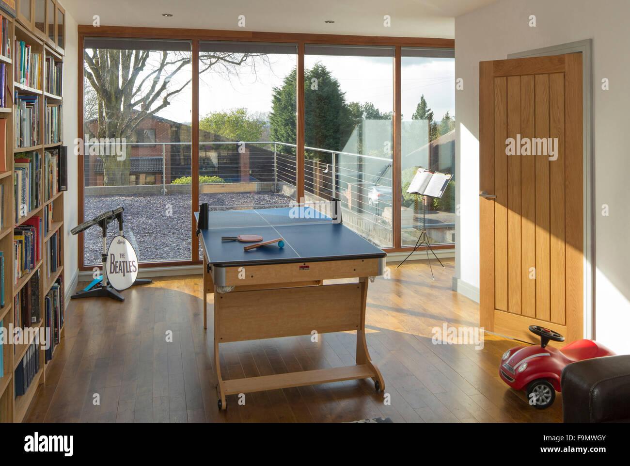 Sala giochi mostra pavimento in legno e tavolo da ping pong. Lunghezza di caduta porte scorrevoli di vetro su di Immagini Stock