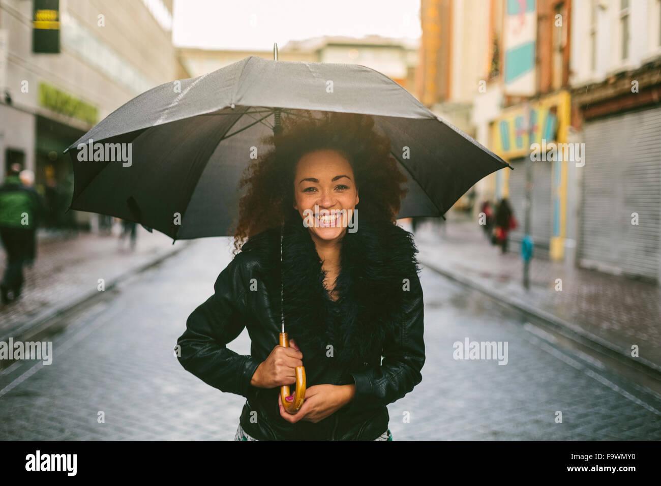 Ritratto di donna sorridente ombrello in un giorno di pioggia Immagini Stock