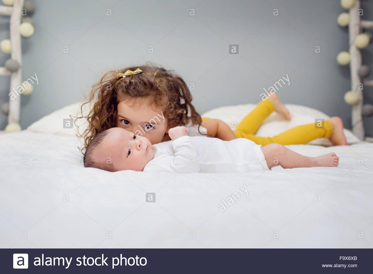 Big Sister kissing neonato sdraiato sul letto Immagini Stock