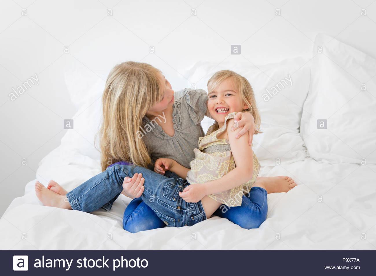Big Sister azienda sorella più piccola tra le sue braccia su un letto Immagini Stock
